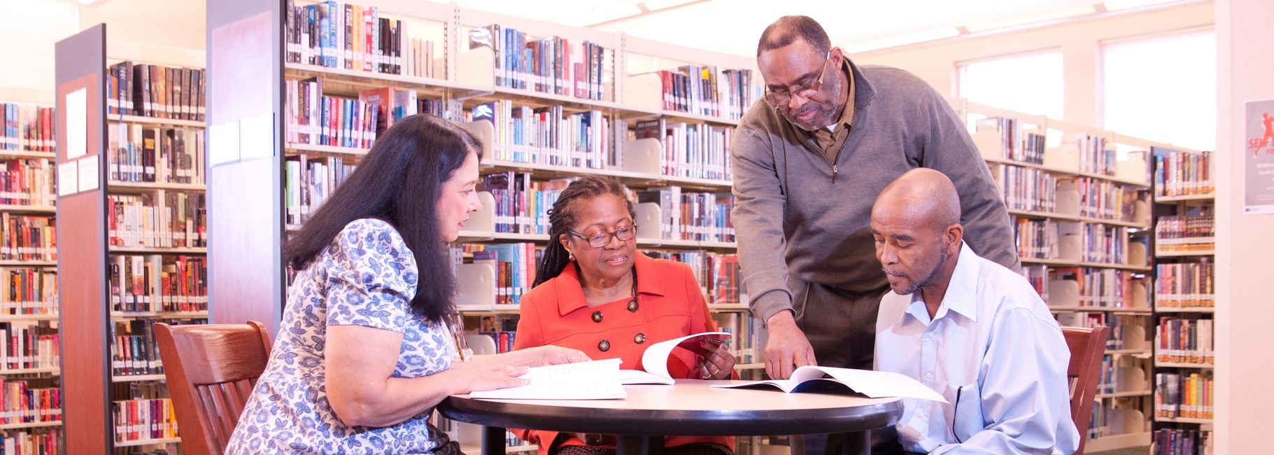 One adult teacher three adults sitting at a table in the library