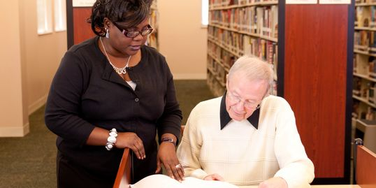 Woman showing older man something in a book at desk
