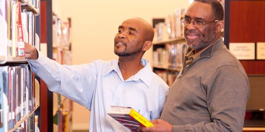 Two men looking for books on a bookshelf at library