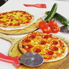 authentic wood fired pepperoni pizza with vegetables on wooden boards