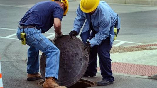 Men lifting manhole covers very hazardous