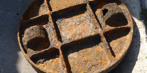 Corroded manhole cover with holes and degraded