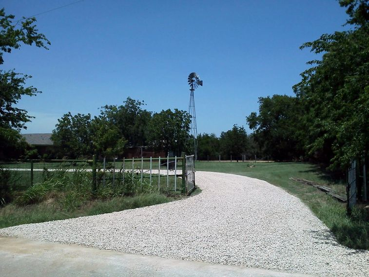 Entrance to a restored gravel driveway with crushed limestone in Ponder, Texas.