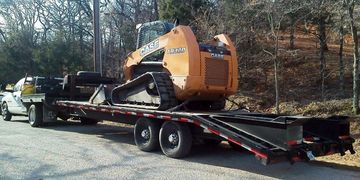 Equipment, skid steer, track loader, attachment hauling Decatur, Texas.