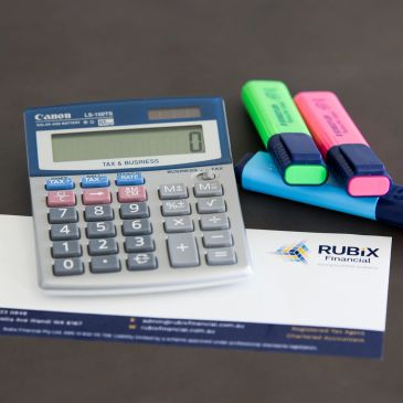 Calculator, highlighters and Rubix Financial stationary on a table