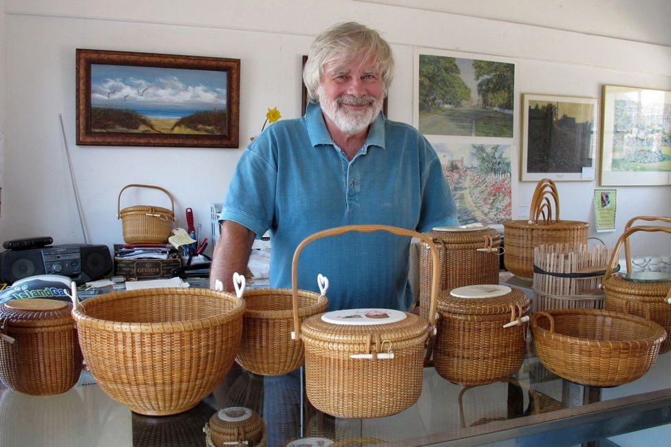 Gerald L. Brown in his shop with some Nantucket lightship baskets he made.