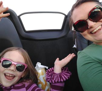 Mother and Daughter wearing sunglasses in convertible