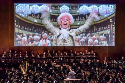Behind a symphony orchestra, a movie screen shows Mozart, a man 18th century clothes, conducting.