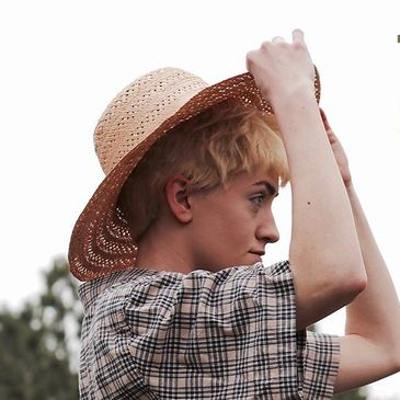 A young girl with short, fair hair and plaid shirt puts on a farming hat and looks into the distance