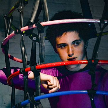 A teenage boy with sinister makeup and jumpsuit looks out from within a bizarre circus cage.