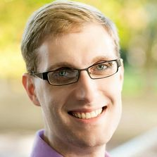 Photograph of editor Dustin K. Britt. Smiling at the camera with glasses and short blond hair.