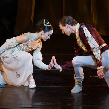 A male and a female ballet dancer in Elizabethan dress kneel and place their hands palm-to-palm