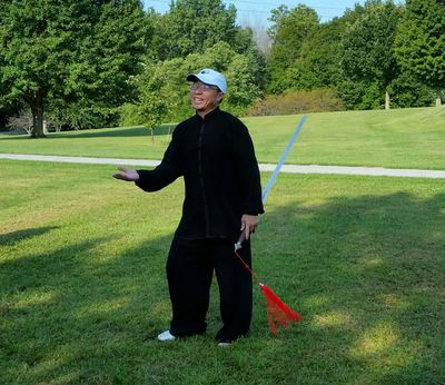 Master Zhichao Ling teaches tai chi and taiji sword in Noblesville and Kokomo Indiana. Smiling Chinese tai chi instructor with sword standing in park on summer day.