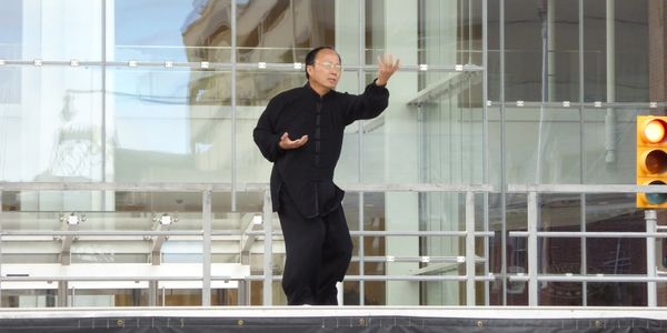 Master Zhichao Ling demos Chen 56 Forms Taiji (Tai Chi) at the Indianapolis Sister Cities event. Chinese Tai Chi master performing Chen style taiji on a stage among city buildings.