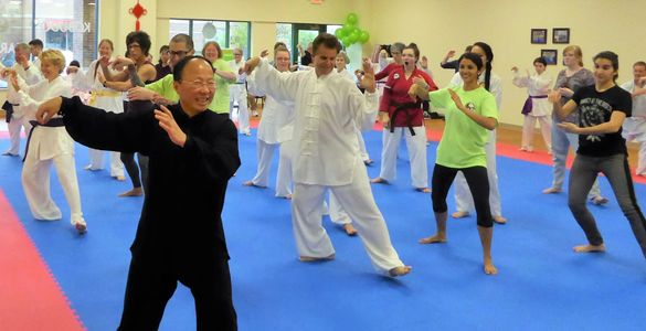 Master Zhichao Ling and students practice Yang 24 Forms Taiji on World Tai Chi & Qigong Day. Traditional Chinese tai chi instructor leading students in martial arts dojo.