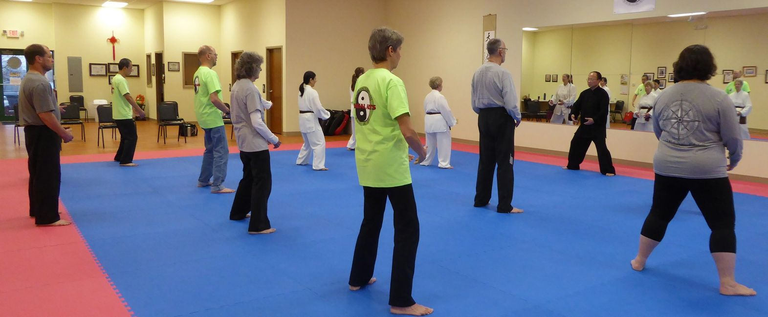 Tai Chi for Health students stand and meditate with instructor.  Tai chi studio with class practicing standing meditation (zhan zhuang) with Master Ling.