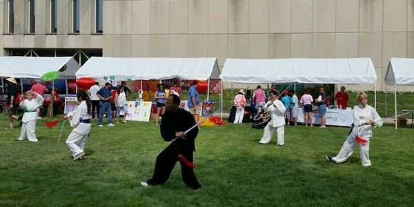 Master Ling and students demonstrate Tai Chi sword (Taiji Jian) at the Indy Chinese Festival Indiana. Tai chi sword form with Taiji master and students in urban public park.