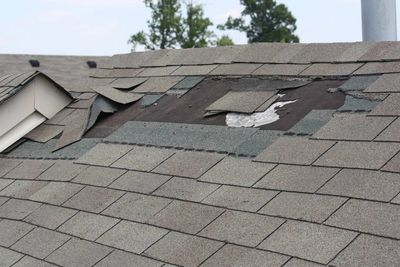 Roof shingles damaged by the wind and repair about to take place.