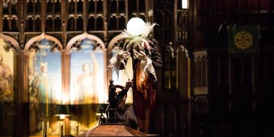 A etherial puppet in a tailcoat with a magical glowing head glides in a beautiful church.
