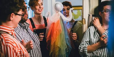 A Rainbow Puppet Character from Loaded Object Theatre's Busy Being Ze, Puppeteers in bright colours.
