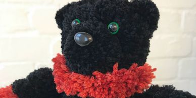 A black and orange pompom bear with lovely green eyes.