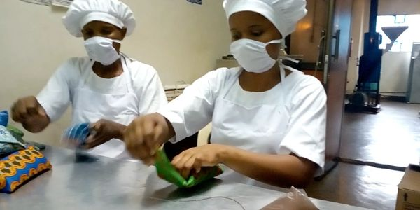 Choice Coffee Co Ltd workers sewing Kitenge cloth onto Kilimanjaro Coffee packages