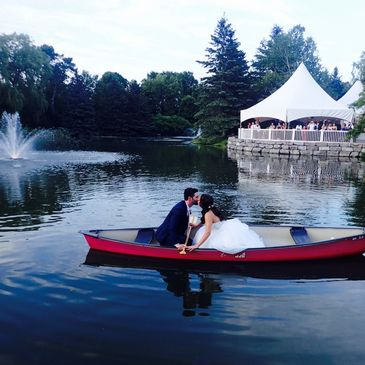 Nestleton Waters Inn bridal couple in our signature red canoe by fountain. Living the dream!
