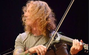 man with long hair playing electric violin