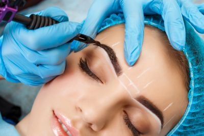 Graceful Glamour cosmetologist applies permanent makeup, permanent eyebrow, eyebrow tattoo