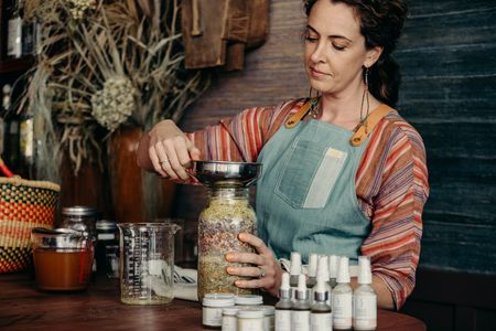 formulators, maker, handcrafted, dry herbs, woman, apron, cleansing cream, oil serum, day cream, shea whip, glass beaker, woven basket, apple cider vinegar, mason jar, herbal infusion