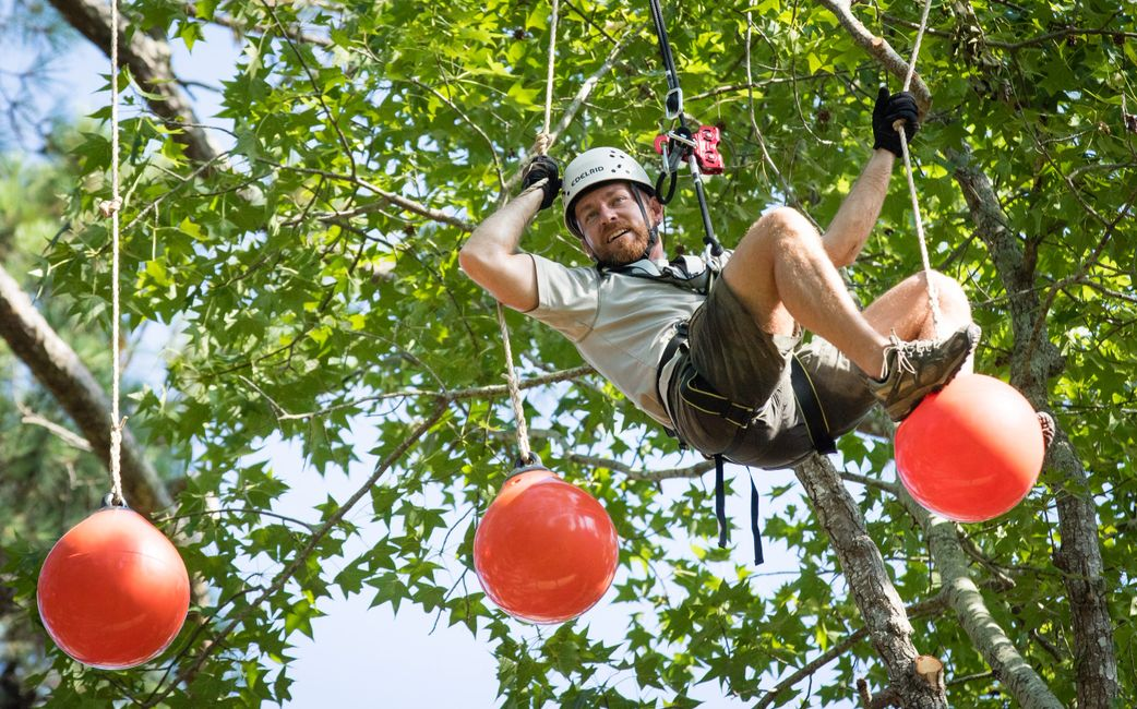 Man on challenge course activity on outdoor ropes course in Wisconsin.