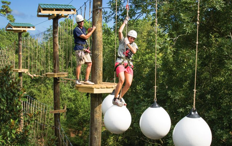 College students enjoying a team-building activity on aerial adventure park in Michigan.