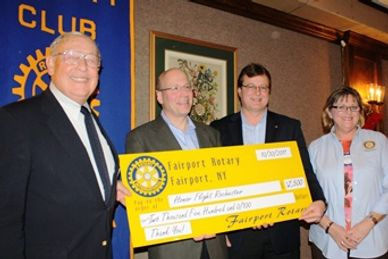 Fairport Rotary presents funds to Honor FLight of ROchester, a charitable organization.