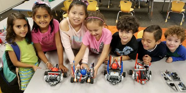 young students playing with robots.
