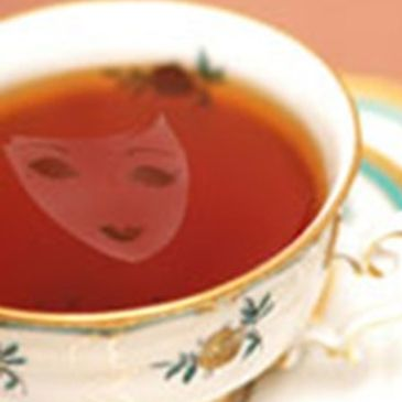 Smiling theatre mask super-imposed in a cup of tea