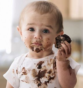 Image of a cute toddler messy with dark chocolate