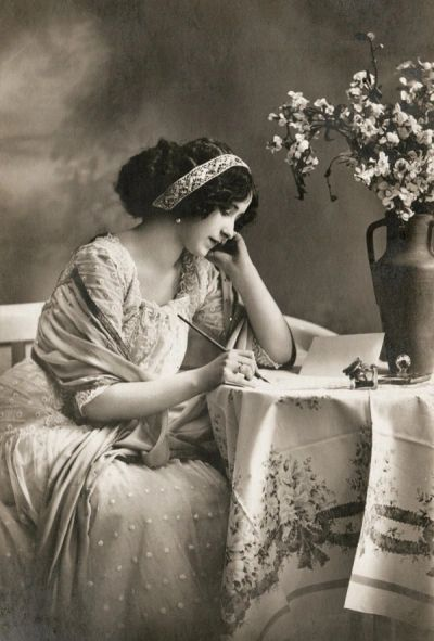 Black and white image of an Edwardian era woman writing at a table
