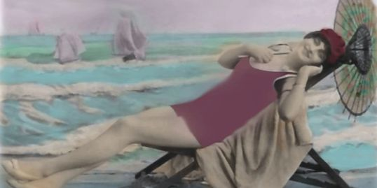 Colorized image of 20's era woman lounging on chair at the beach