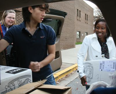 High school students loading boxes of food they collected into a pickup car.