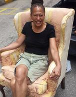 Mrs. Laura Washington sitting in the chair Jasmine re-upholstered for her during our summer program