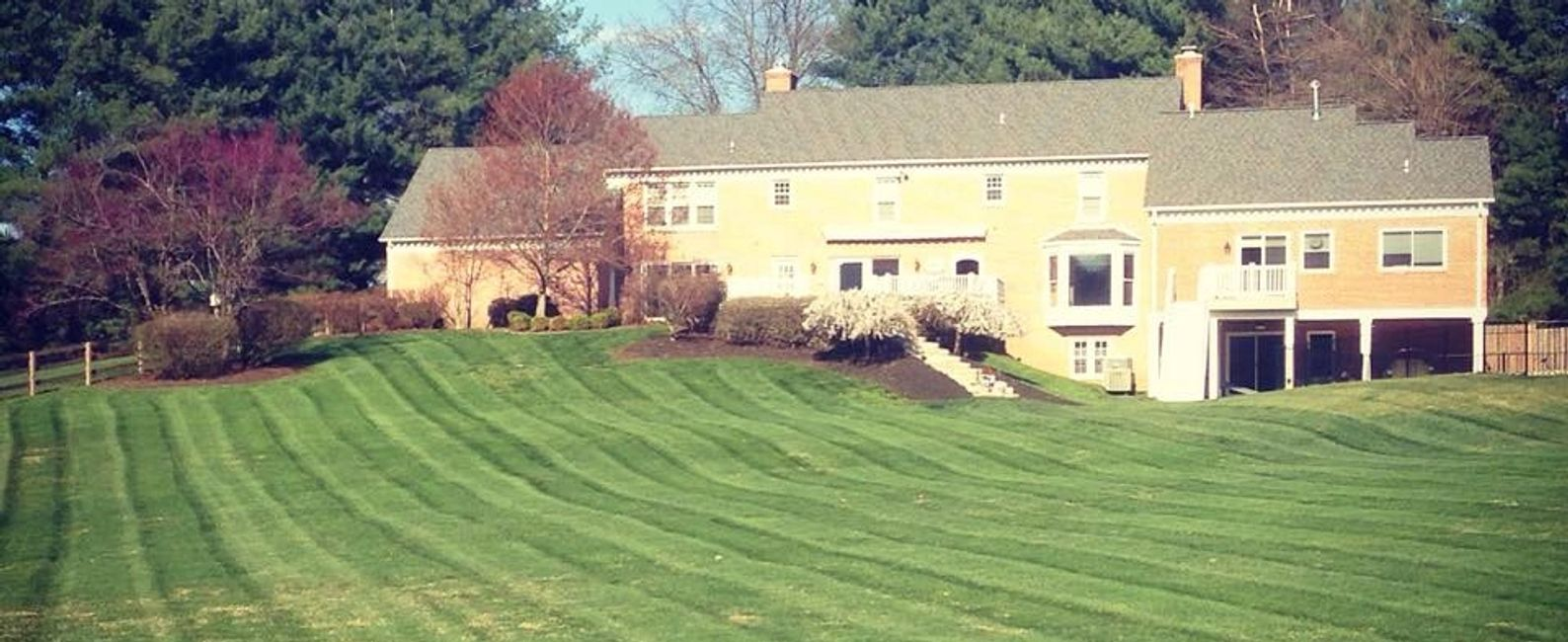 Westminster MD lawn care company. Beautiful landscapes and green grass. Yellow house | LaneScapes