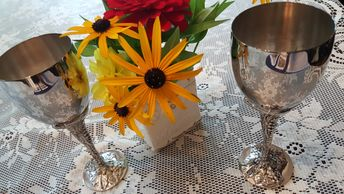Two pewter wine glasses with a bouquet of flowers.