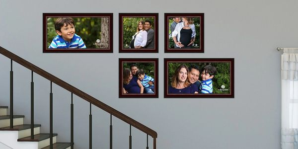 Stairwell wall with gallery collection of five framed family portraits