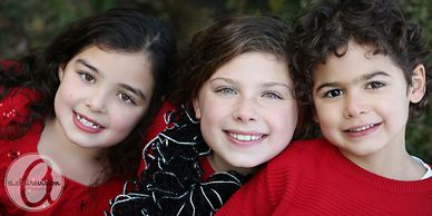 close-up portrait of three sibling children smiling