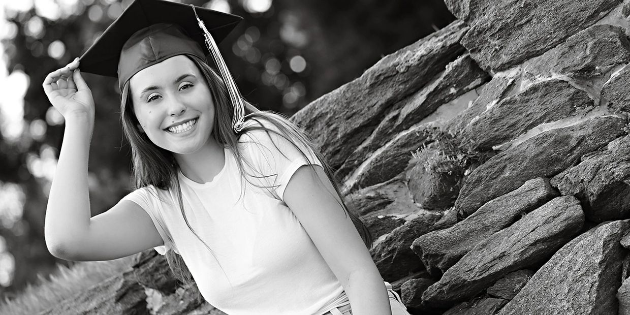black and white picture of high school senior girl with cap and tassel leaning on stone wall