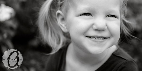black and white picture of young child smiling with pigtails