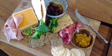 Cheese and meat gourmet grazing platter with crackers, chutney, salami, ham, olives
