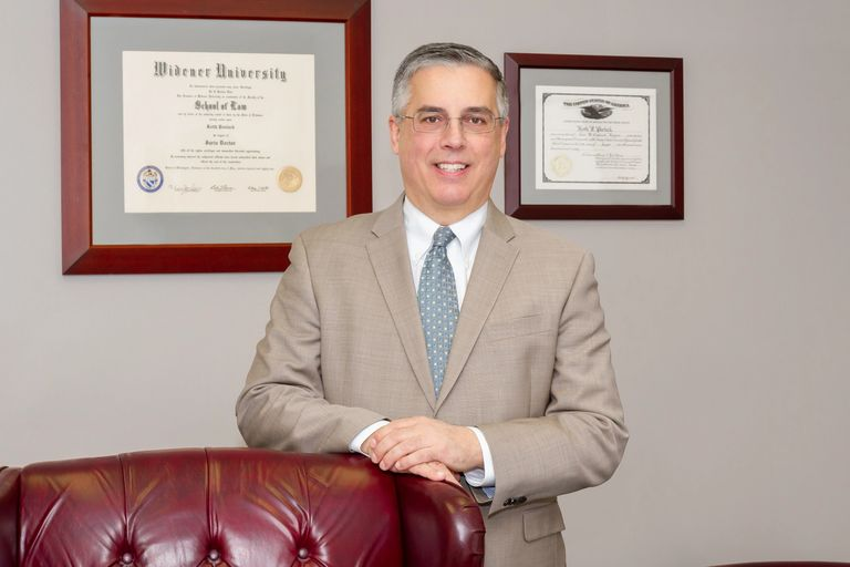 Attorney Pavlack posing for a photo in his office with his diplomas hanging on the wall behind him a
