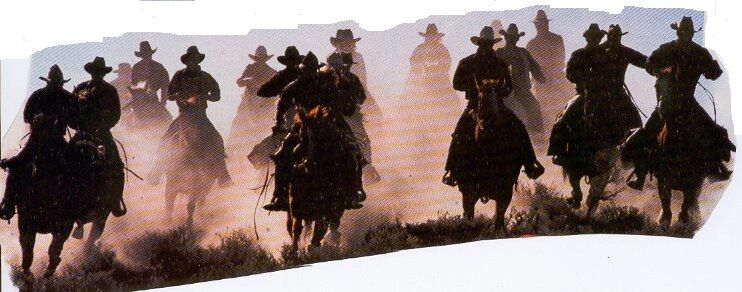 men (cowboys) ride on horseback as the sun is setting. the ground is dusty