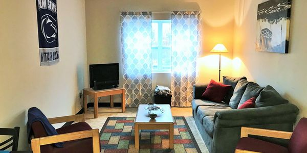 Living room furnished with sofa, table and side chair and window blind/shade.